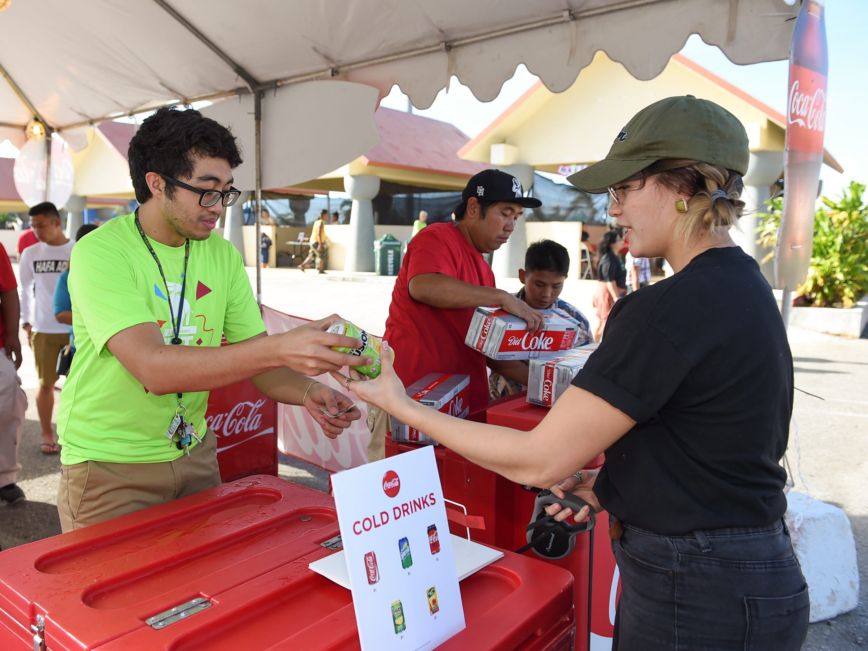 Aria Gumataotao purchased a beverage from Bank of Guam employee Kameron Anderson during the Bank of Guam Ifit Run and Block Party at Chamorro Village in Hagåtña, March 9, 2019.