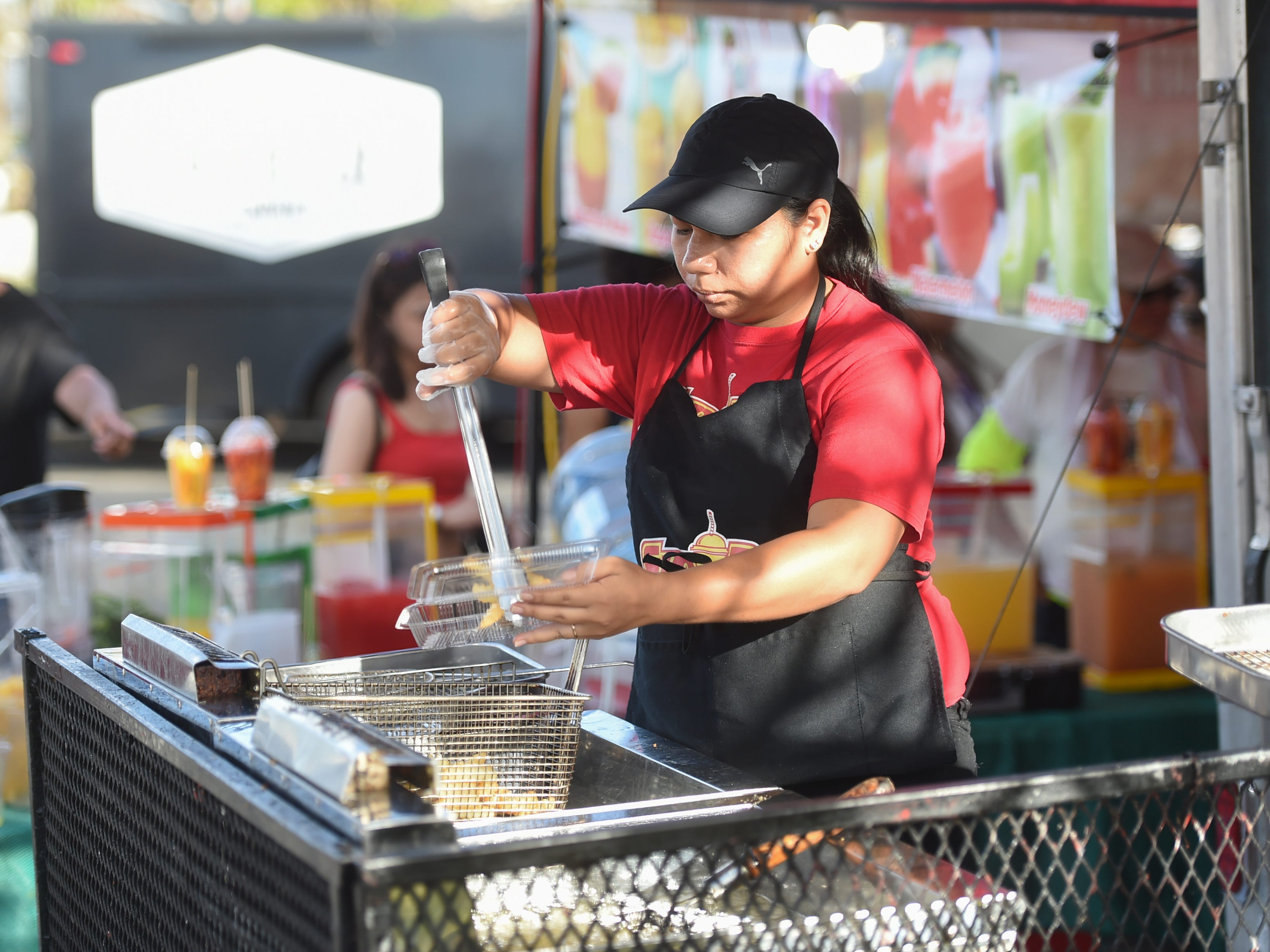 Sip'nDip Guam employee Venisha Blas prepares an order of fries during the Bank of Guam Ifit Run and Block Party at Chamorro Village in Hagåtña, March 9, 2019.