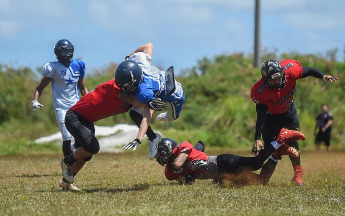 """The Outlaws' Hans Reppuhn stops Southern Cowboys player Chance """"Boo"""" Benefield in mid-air during a Budweiser Guahan Varsity Football League game at Eagles Field in Mangilao, March 9, 2019."""