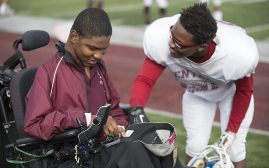 FILE – Emanuel Duncan, who has Duchenne Muscular Dystrophy, chats with friend and player Bryan Rutland, 17, at a football practice for Lawrence Central High School, Oct. 13, 2015.