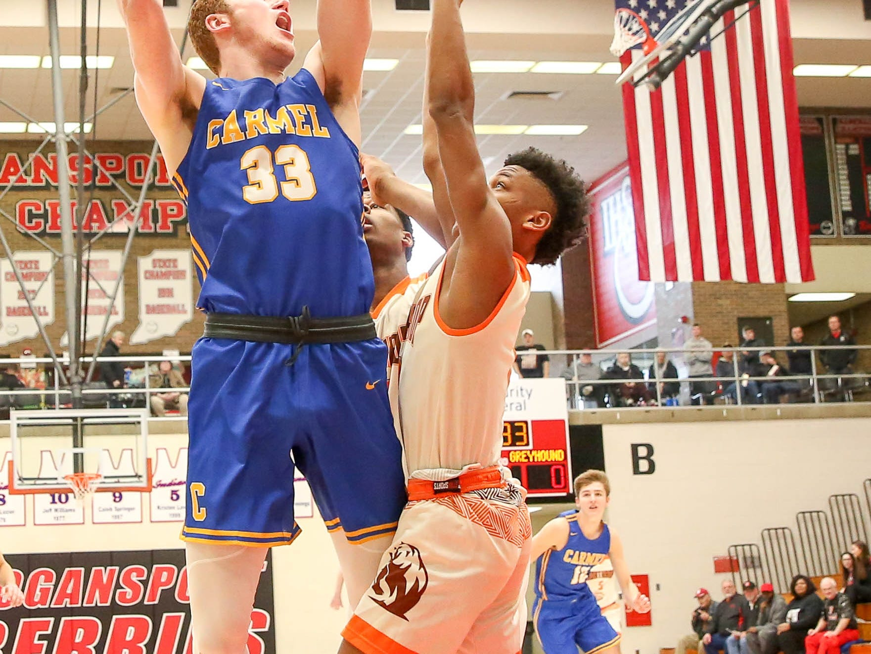 Carmel's John Michael Mulloy (33)takes to the air for a shot during the first half of Carmel vs. Fort Wayne Northrop High School in the IHSAA Varsity Boys Regional Semifinals held at Logansport High School, March 9, 2019.