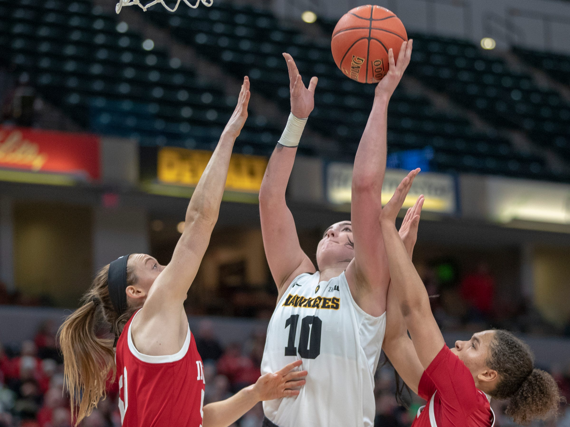 Megan Gustafson of the Iowa Hawkeyes puts up a shot as she is defended by a duo of Hoosier players, Indiana vs. Iowa, Women's Big Ten Tournament, Bankers Life Fieldhouse, Indianapolis, Friday, March 8, 2019. Iowa won 70-61.