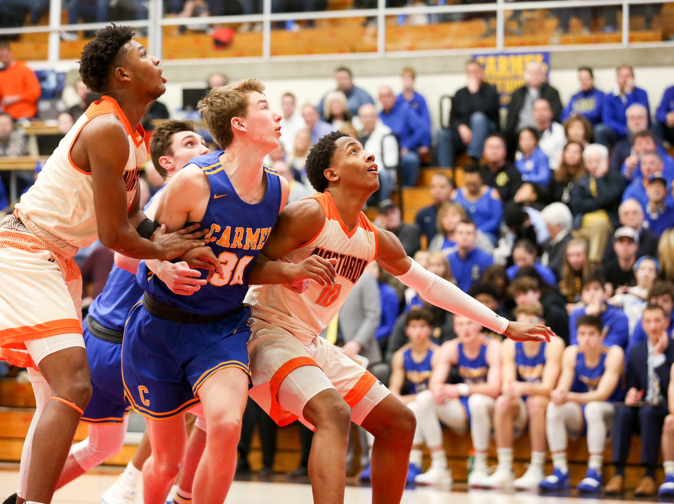 Players watch a 3 point attempt ready to try to get the rebound if missed during the second half of Carmel vs. Fort Wayne Northrop High School in the IHSAA Varsity Boys Regional Semifinals held at Logansport High School, March 9, 2019.
