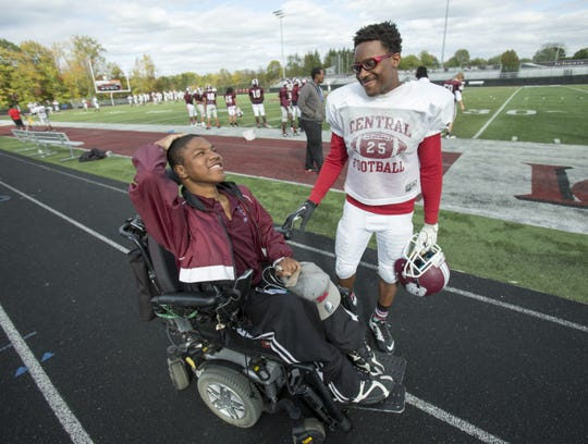 Emanuel Duncan, who has Duchenne Muscular Dystrophy, chats with friend and player Bryan Rutland, at a football practice for Lawrence Central High School, Indianapolis,, Oct. 13, 2015.