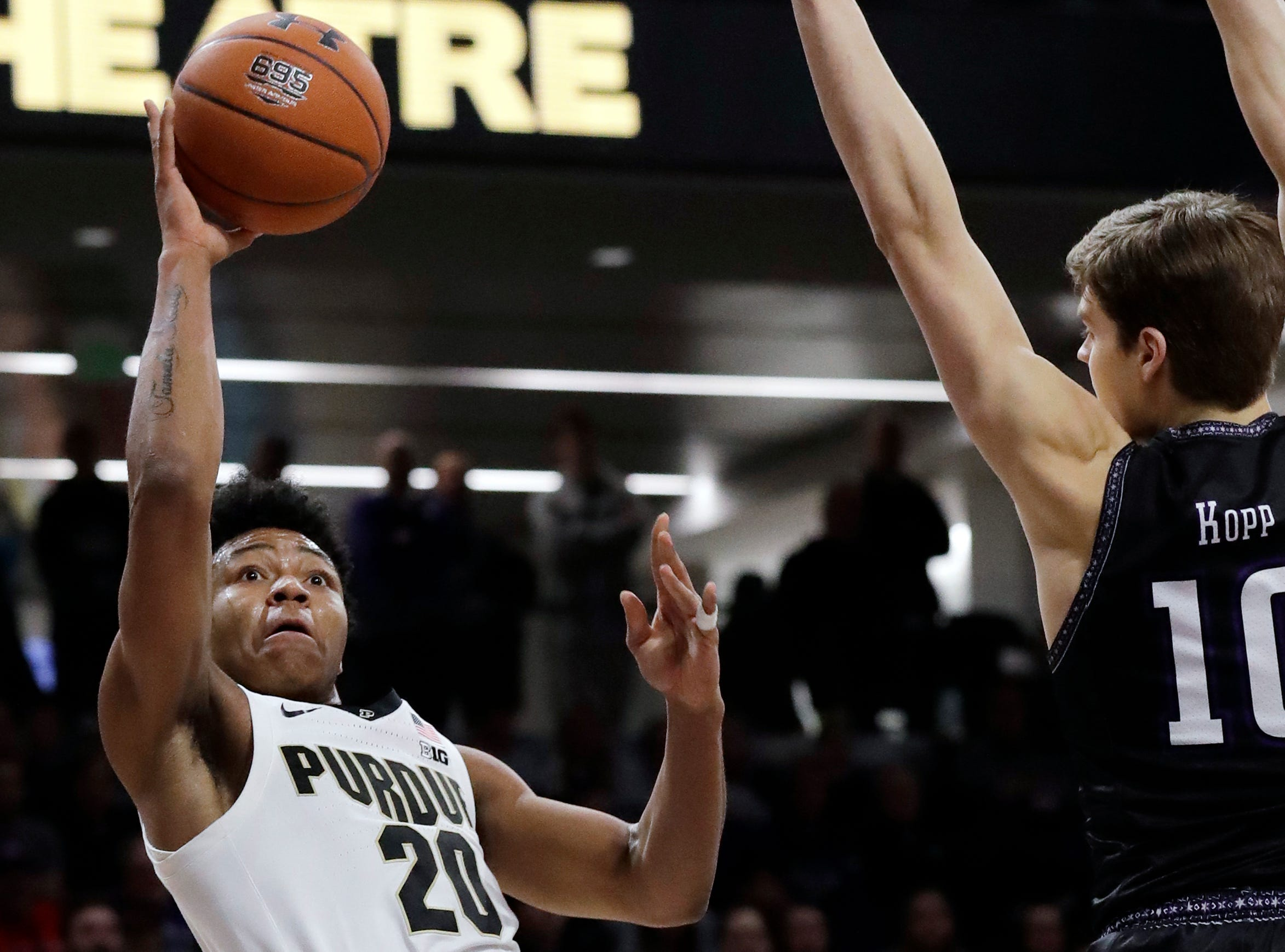 Purdue guard Nojel Eastern, left, shoots against Northwestern forward Miller Kopp during the first half of an NCAA college basketball game Saturday, March 9, 2019, in Evanston, Ill.