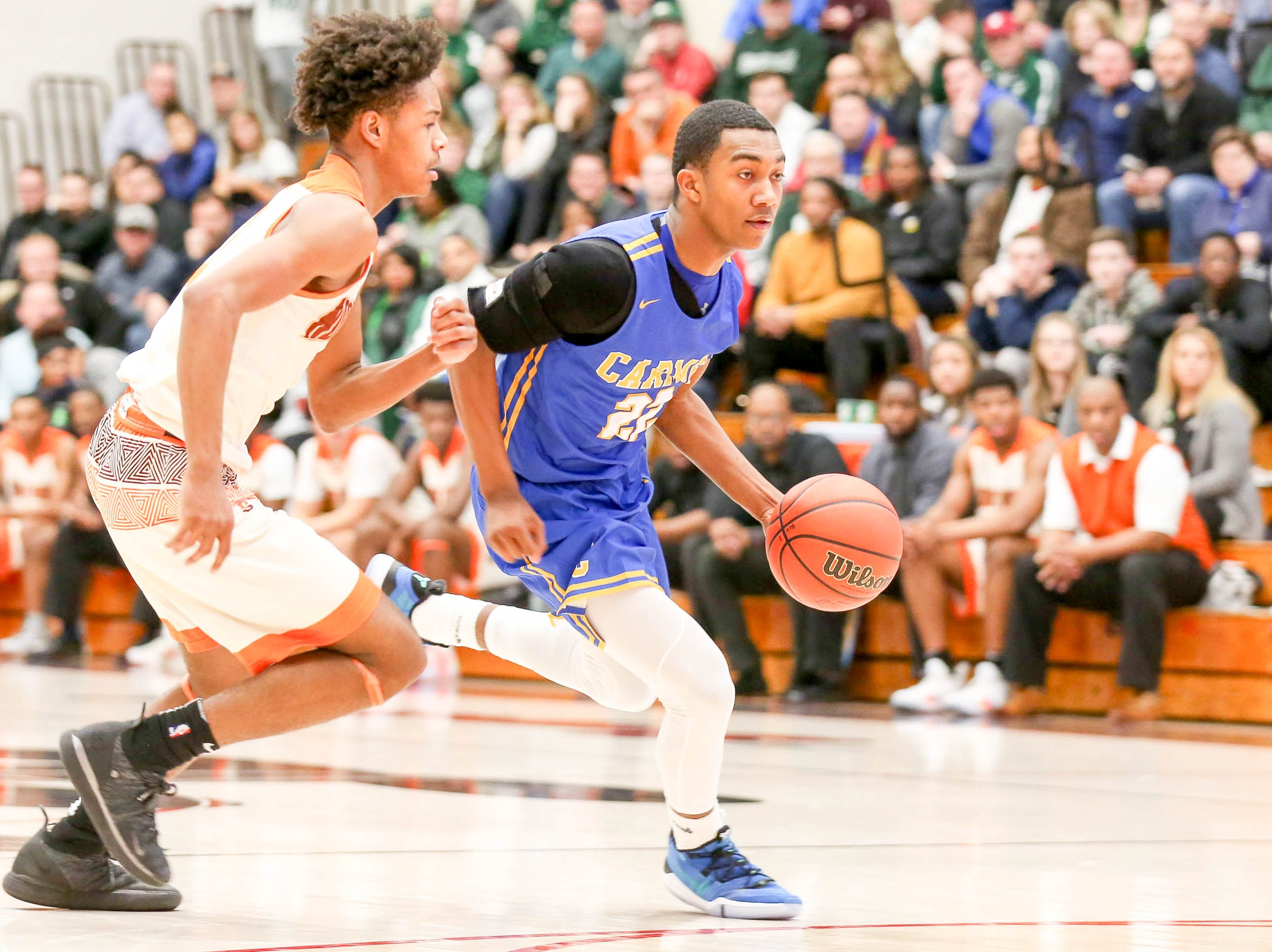 Carmel's Robert Fry (22) works to get around Forth Wayne Northrop Tenoah Ridley (3) during the second half of Carmel vs. Fort Wayne Northrop High School in the IHSAA Varsity Boys Regional Semifinals held at Logansport High School, March 9, 2019.