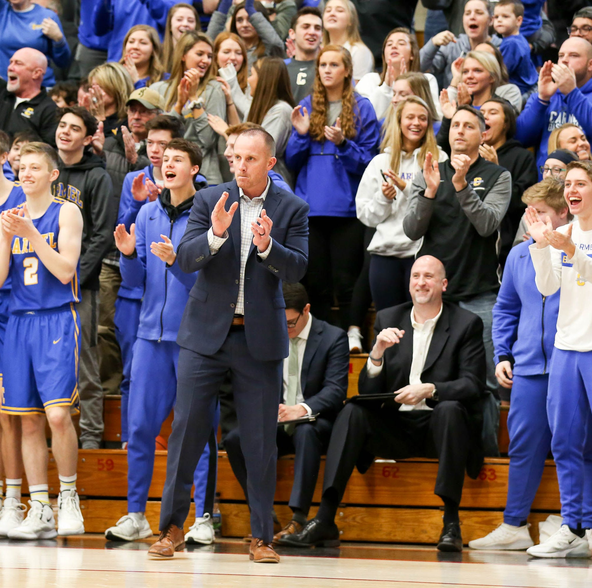 Carmel Coach Ryan Osborn, players, and fans begin to celebrate as the final seconds of the games has them at at 16 point lead during the second half of Carmel vs. Fort Wayne Northrop High School in the IHSAA Varsity Boys Regional Semifinals held at Logansport High School, March 9, 2019.