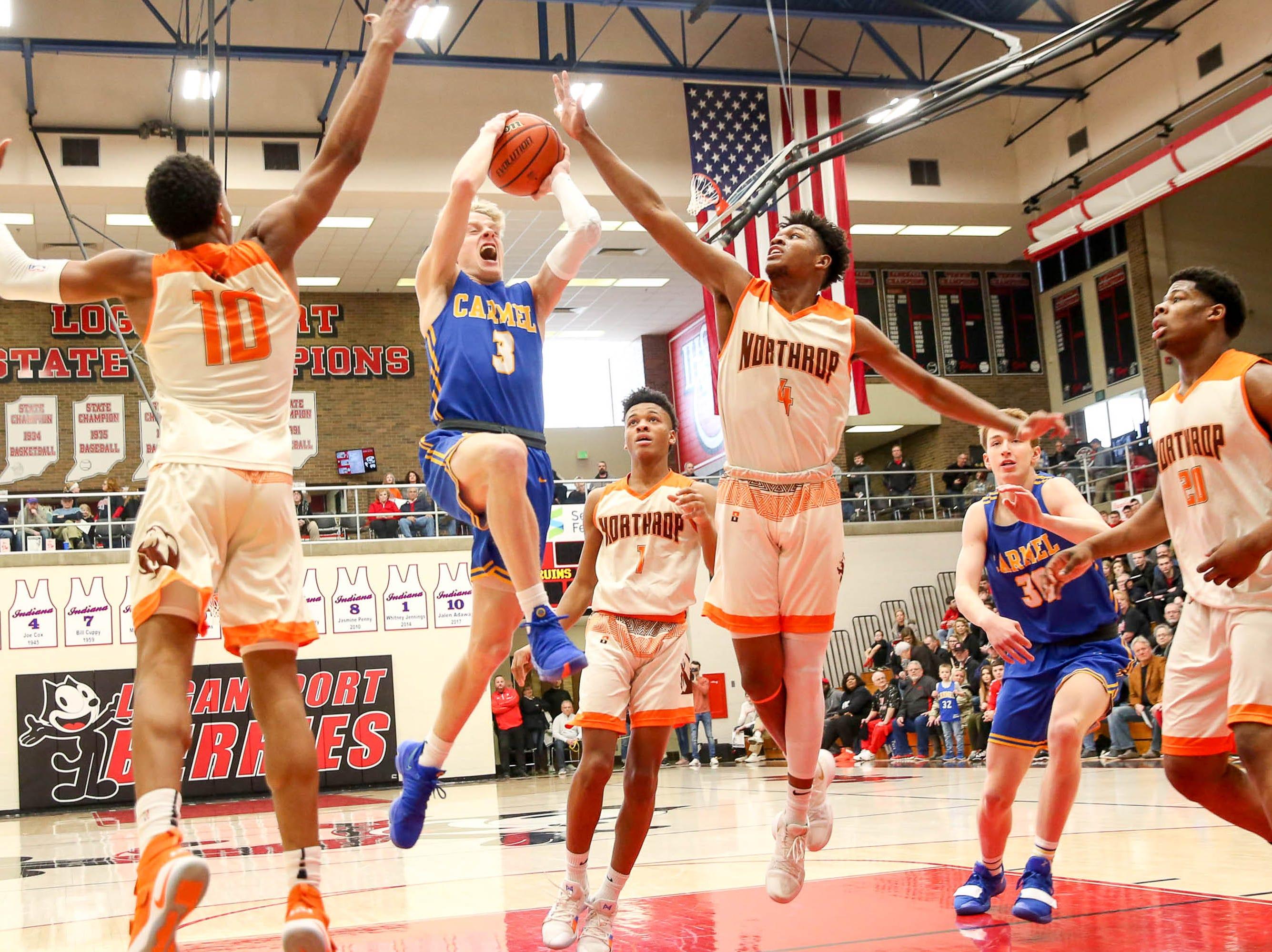 Carmel's Karsten Windlan (3) tries to find space between two defenders during the first half of Carmel vs. Fort Wayne Northrop High School in the IHSAA Varsity Boys Regional Semifinals held at Logansport High School, March 9, 2019.