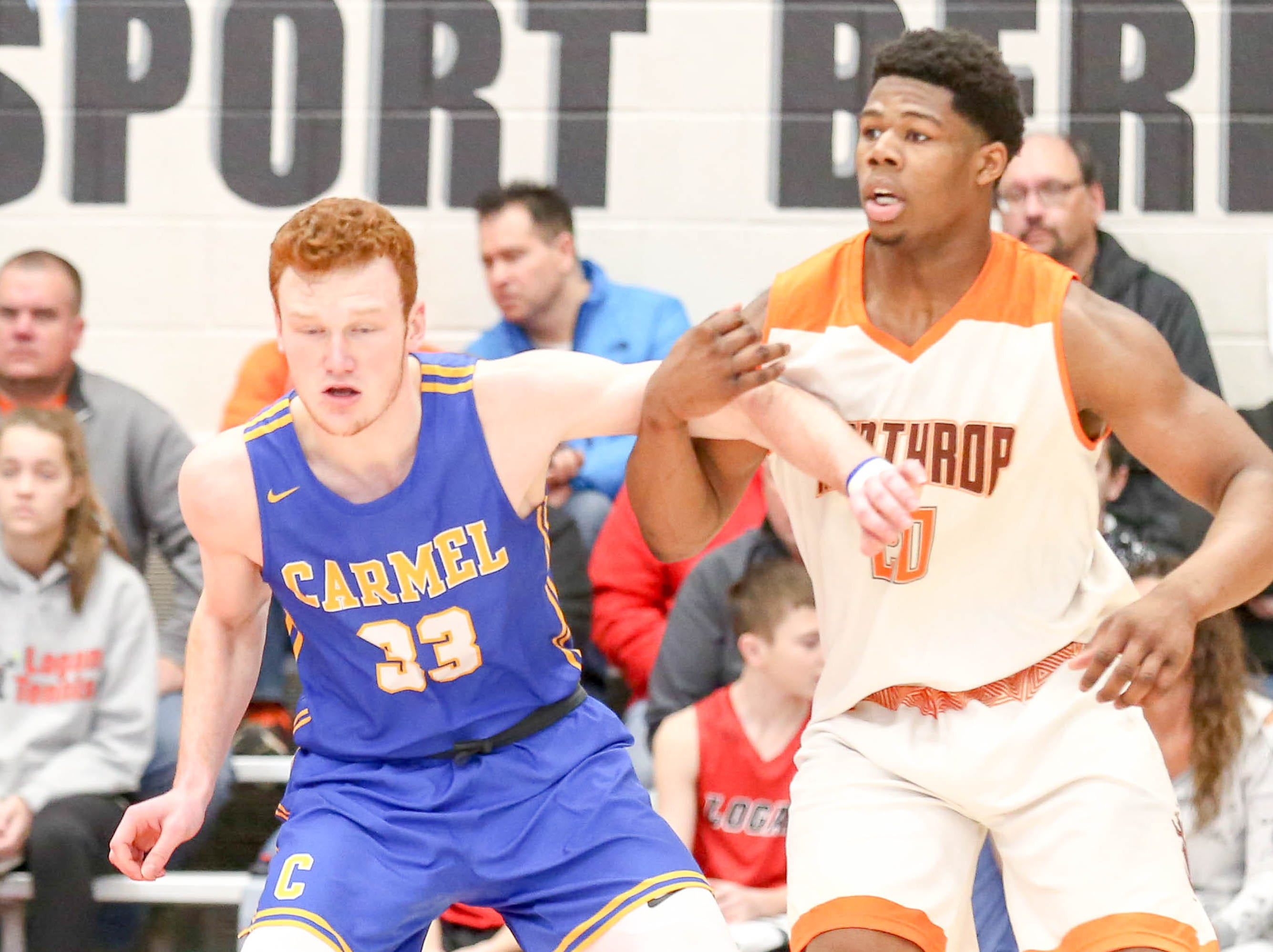 Carmel's John Michael Mulloy (33) and Forth Wayne Northrop Sydney Curry (20) battle for position during the second half of Carmel vs. Fort Wayne Northrop High School in the IHSAA Varsity Boys Regional Semifinals held at Logansport High School, March 9, 2019.