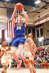 Carmel's John Michael Mulloy (33) finds an opening and goes for the basket against FW Northrop in Saturday's regional final. The Greyhounds beat Zionsville in the nightcap.