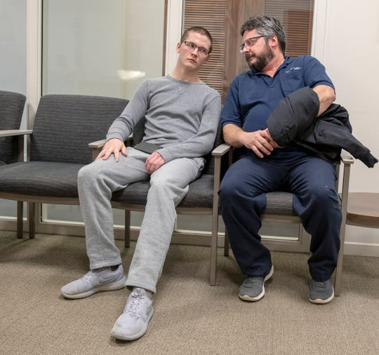 Michael Anderson, 19, sits with his father Mike Anderson before therapy at IU Health Neuroscience Center, Indianapolis, Wednesday, March 6, 2019.