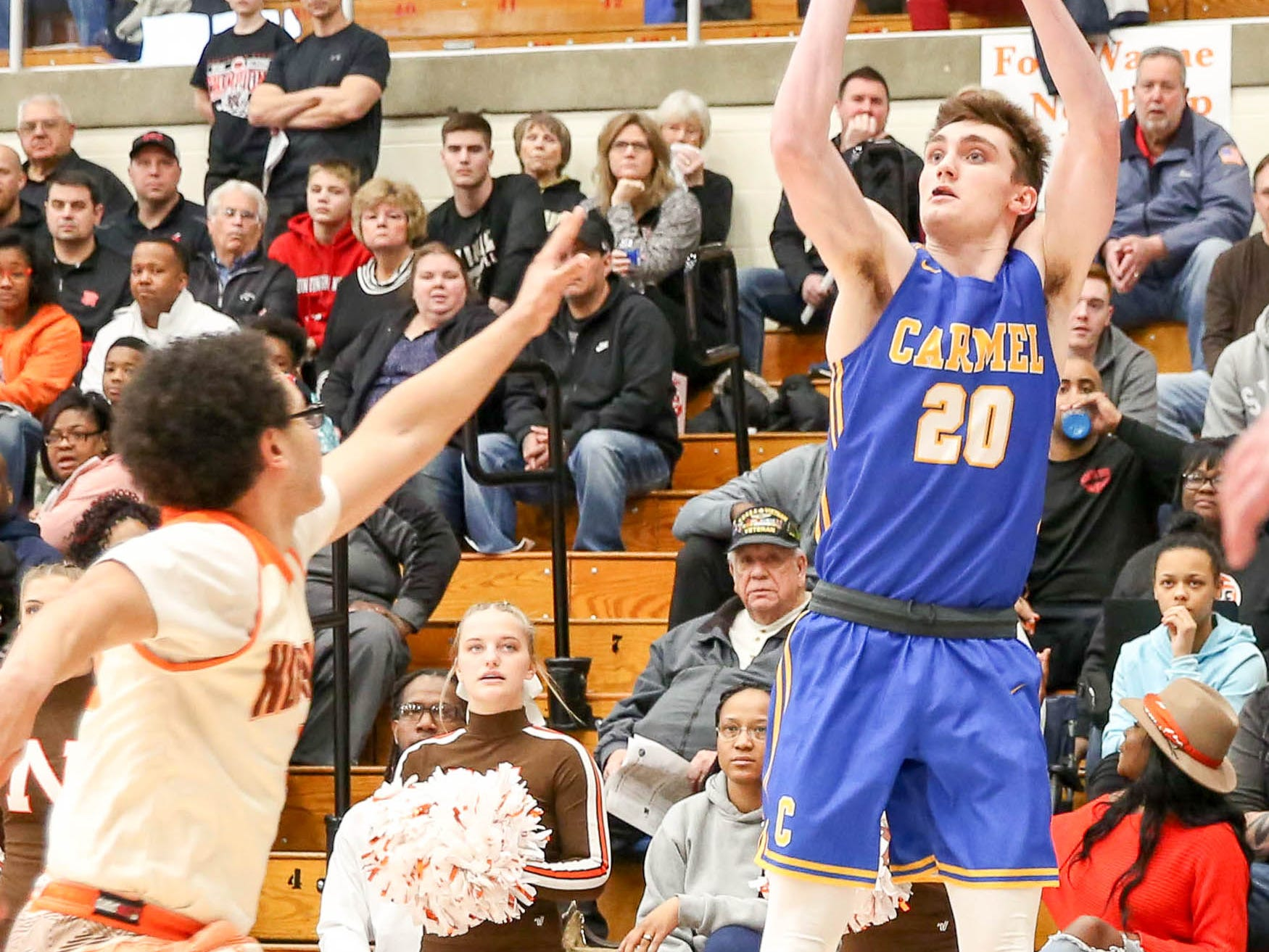 Carmel's Andrew Owens (20) with the 3 point shot during the first half of Carmel vs. Fort Wayne Northrop High School in the IHSAA Varsity Boys Regional Semifinals held at Logansport High School, March 9, 2019.