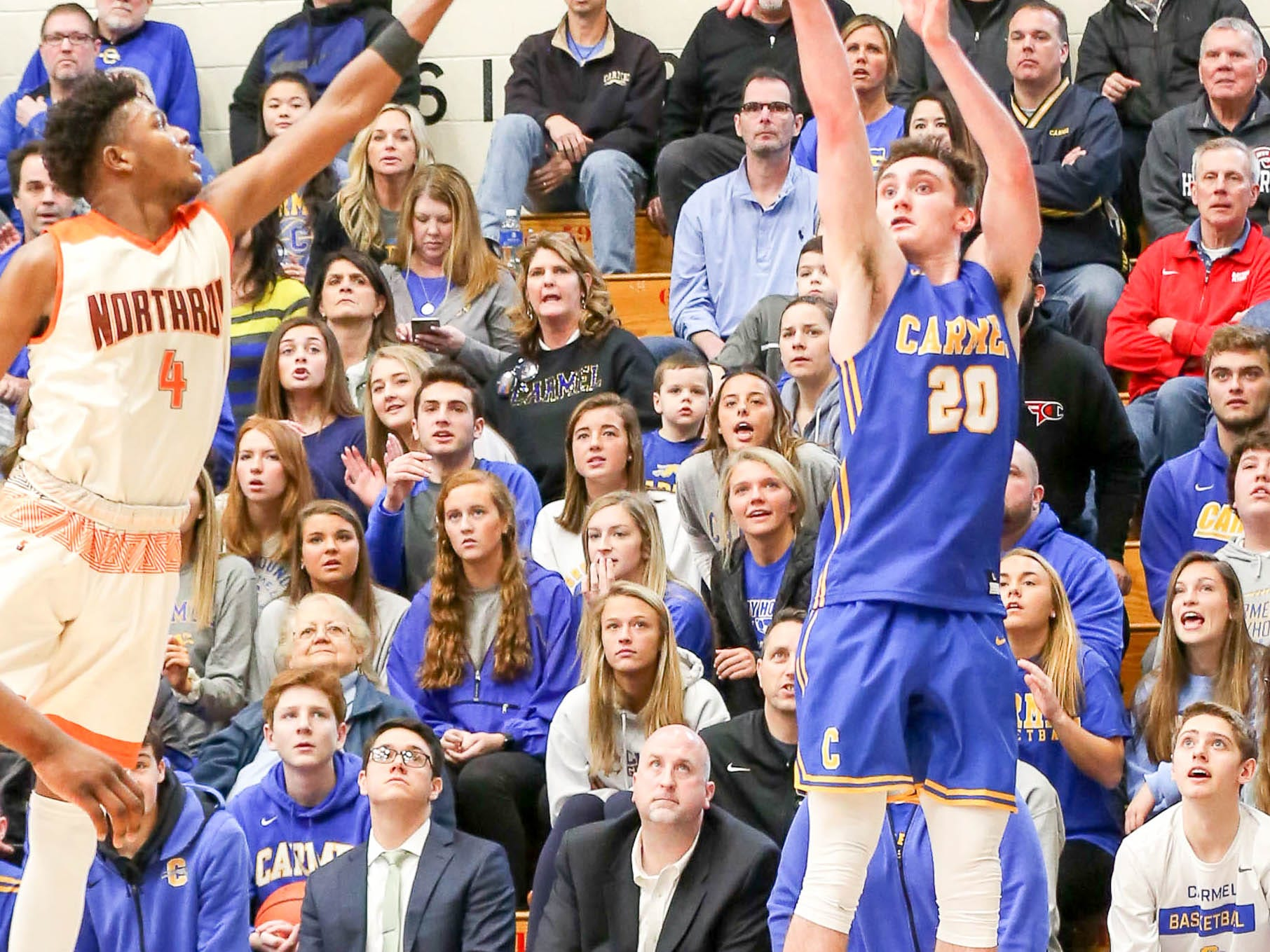Carmel's Andrew Owens (20) makes a 3 point shot during the second half of Carmel vs. Fort Wayne Northrop High School in the IHSAA Varsity Boys Regional Semifinals held at Logansport High School, March 9, 2019.