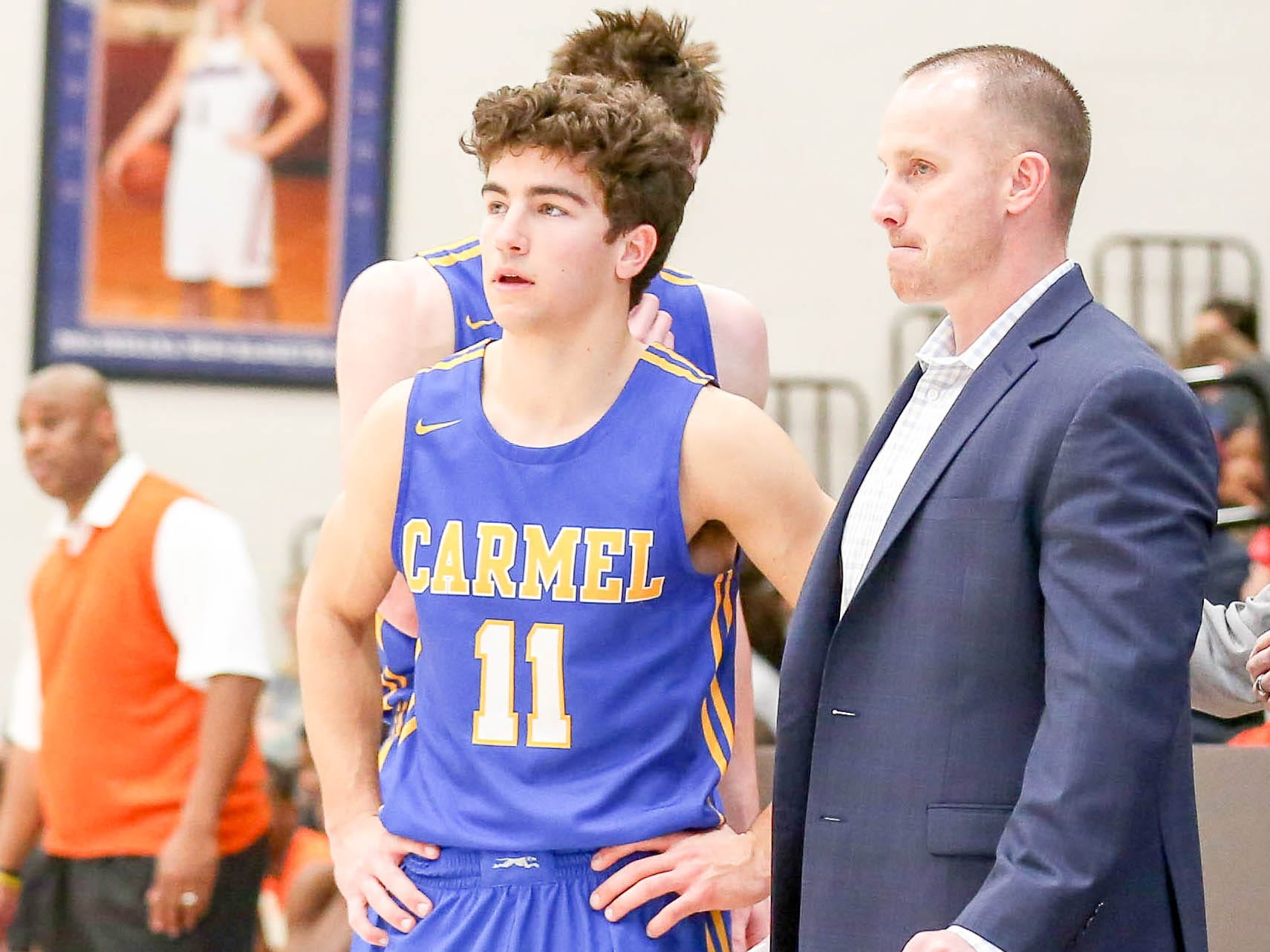Carmel's Luke Heady (11) getting some instructions on the sidelines during the second half of Carmel vs. Fort Wayne Northrop High School in the IHSAA Varsity Boys Regional Semifinals held at Logansport High School, March 9, 2019.