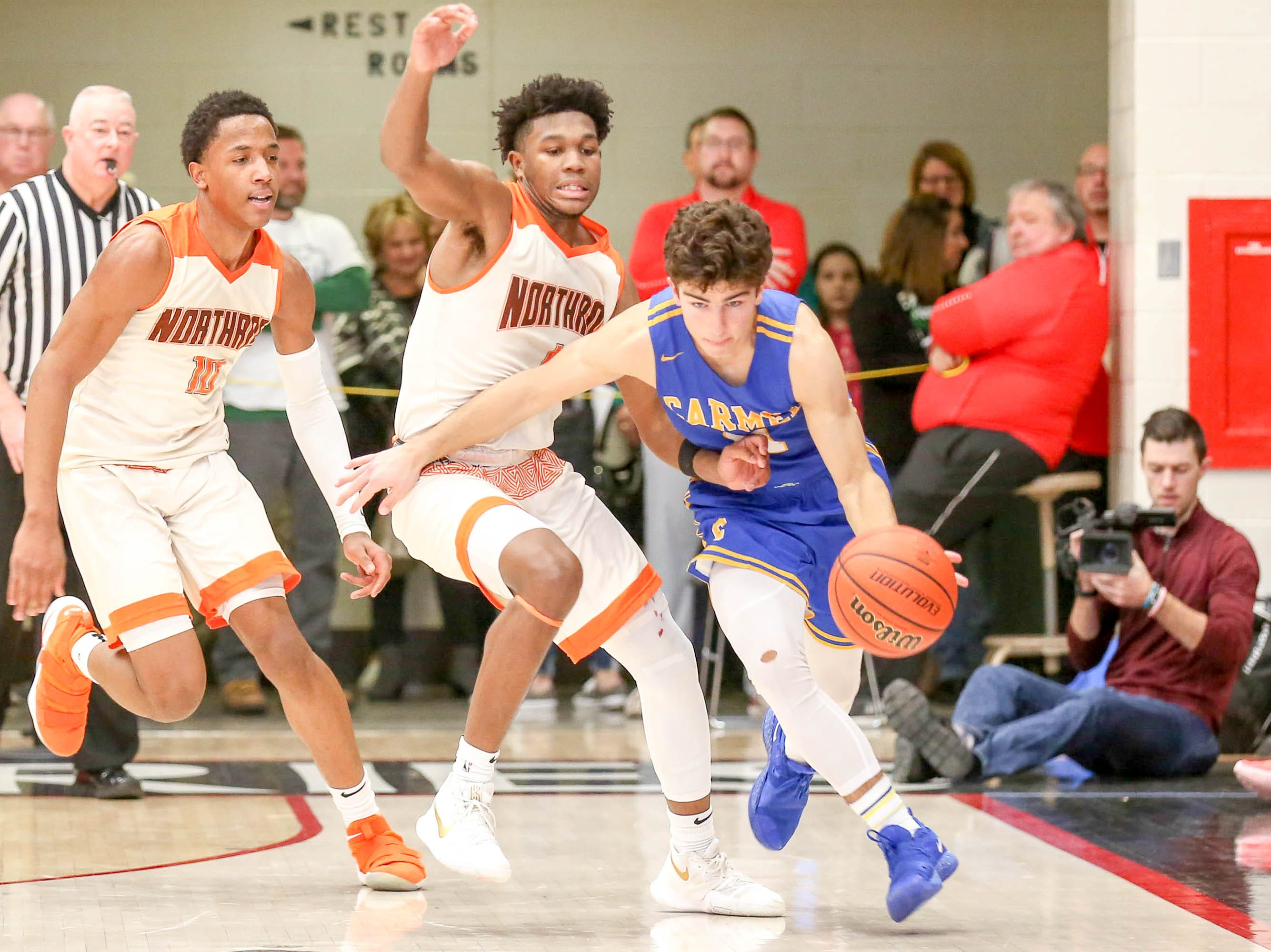 Carmel's Luke Heady (11) draws the foul from Forth Wayne Northrop Qualen Pettus (4) during the second half of Carmel vs. Fort Wayne Northrop High School in the IHSAA Varsity Boys Regional Semifinals held at Logansport High School, March 9, 2019.