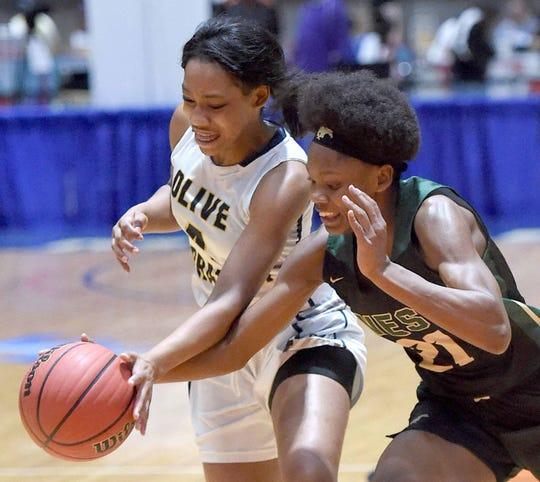 Olive Branch's Brynea Eason (left) and West Jones' Brikayla Gray (21) compete for a loose ball in the finals of the MHSAA C Spire State Basketball Championships at the Mississippi Coliseum in Jackson, Miss., on Friday, March 8, 2019.