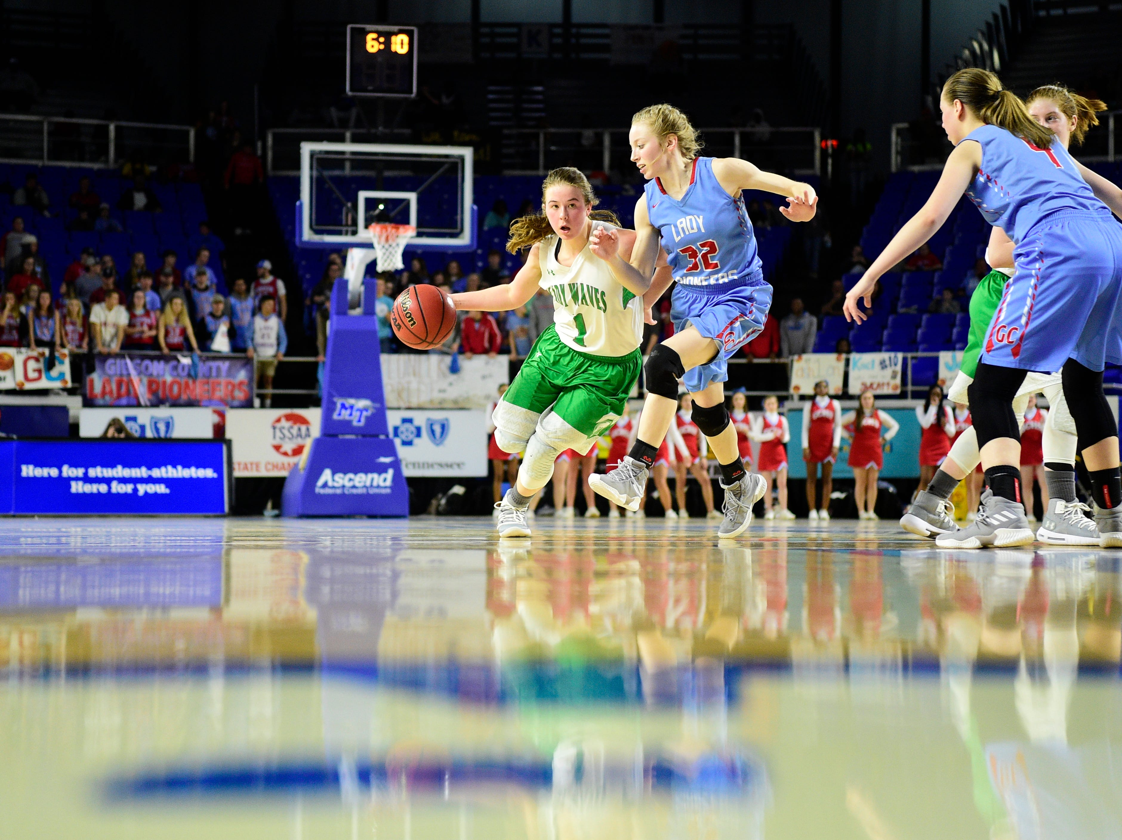 Midway's Caitlyn Ross (1) dribbles past Gibson County's K.J. White (32) during a game between Midway and Gibson County at the TSSAA girls state tournament at the Murphy Center in Murfreesboro, Tennessee on Friday, March 8, 2019.