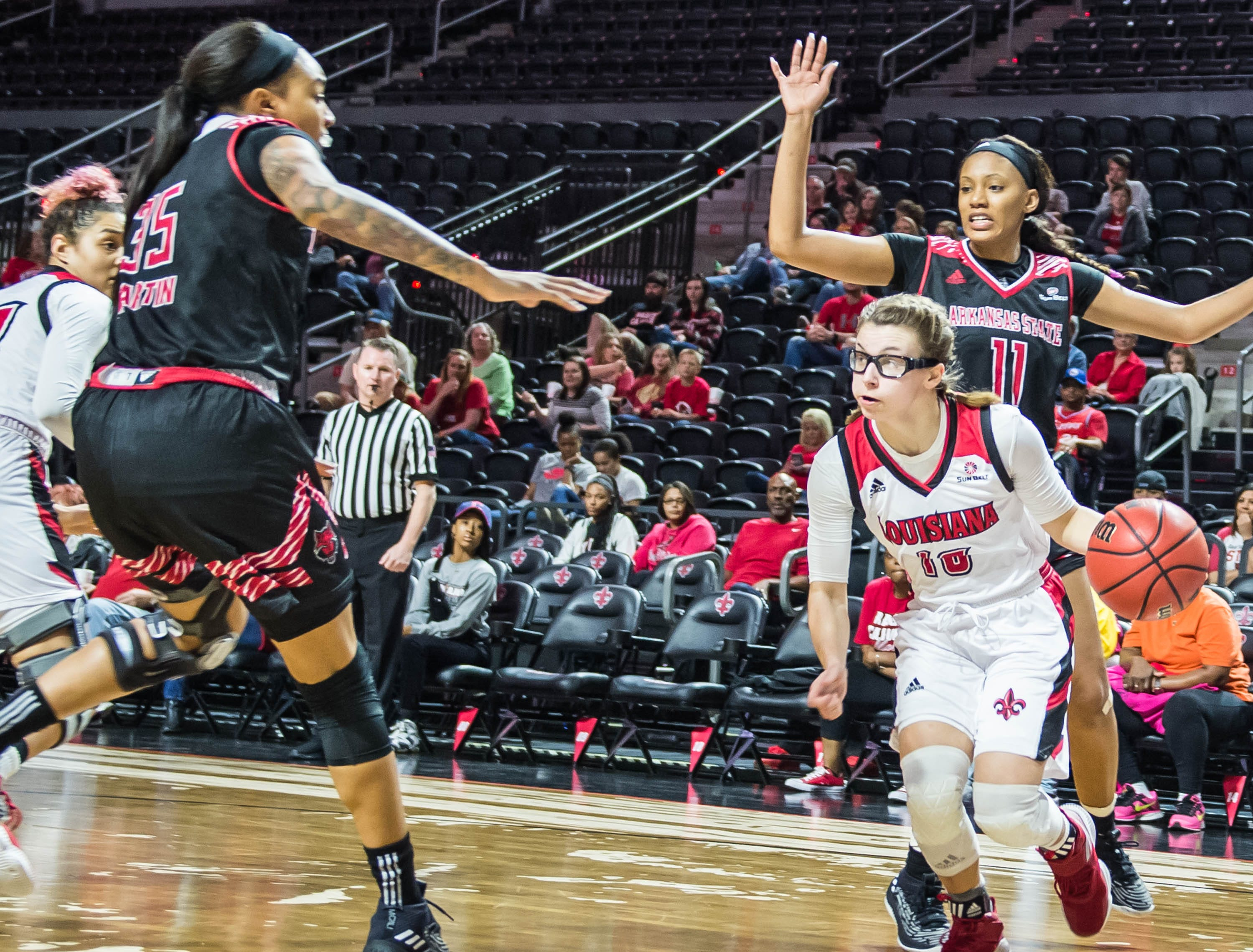 Cajuns guard Andrea Cournoyer (10) looks to pass the ball on the baseline.