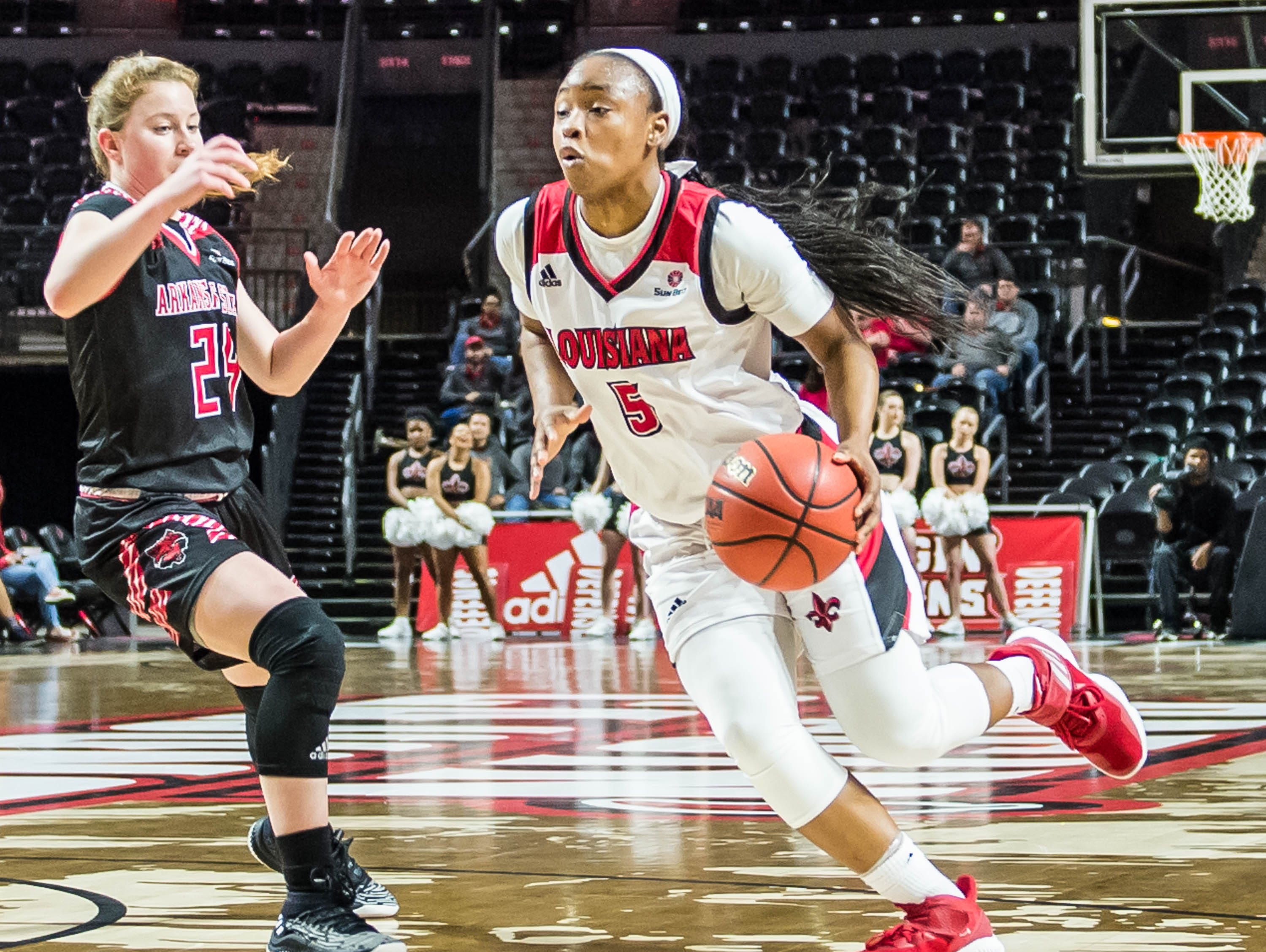 Ragin' Cajuns guard Jomyra Mathis (5) drives with the ball as the Cajuns women's basketball team plays the Arkansas State Red Wolves at the Cajundome on Saturday, March 9, 2019.