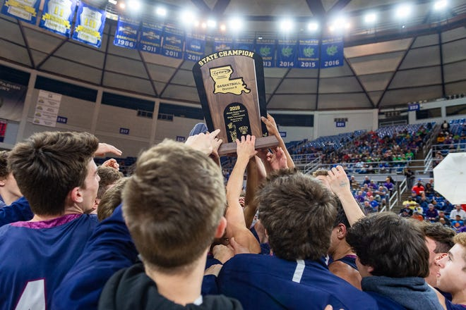 The St. Thomas More Cougars celebrate, hoisting the Division II state championship trophy, after defeating De La Salle in a double-overtime thriller Saturday in Lake Charles.