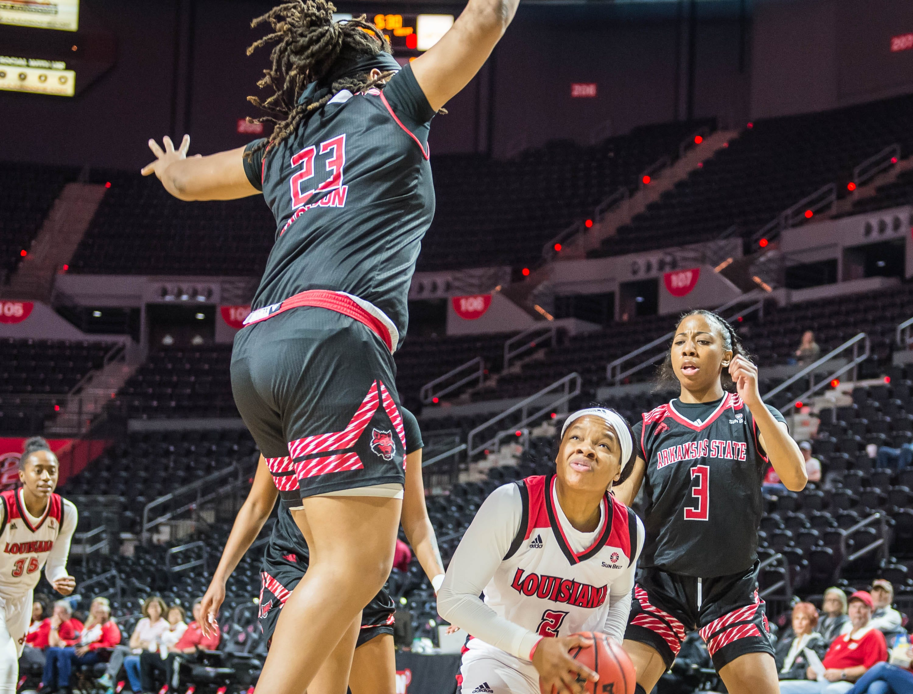 Cajuns guard Brandi Williams (2) with the pump fake to draw Wolves forward Trinitee Jackson (23) up in the air as the Cajuns women's basketball team plays the Arkansas State Red Wolves at the Cajundome on Saturday, March 9, 2019.