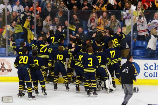 Hartland hockey players celebrate with their student section after beating Trenton, 4-0, in the state Division 2 championship game on Saturday, March 9, 2019 at USA Hockey Arena.