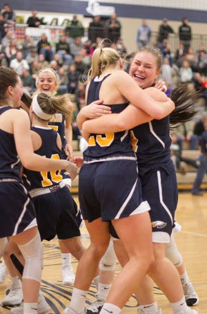 Tess Klavon, right, and Whitney Sollom celebrate Hartland's 42-28 victory over Howell in the district championship game on Friday, March 8, 2019.