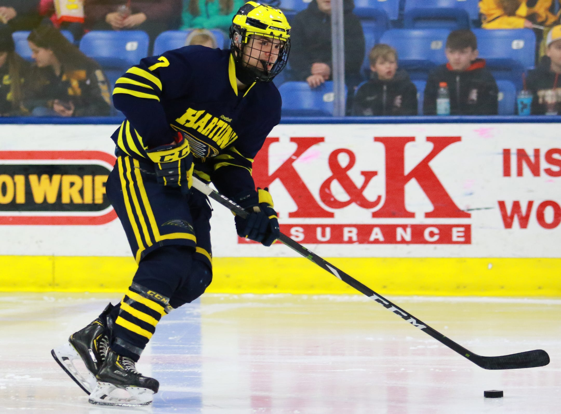 Hartland defenseman Grant Briggs carries the puck in a 4-0 victory over Trenton in the state Division 2 championship hockey game on Saturday, March 9, 2019 at USA Hockey Arena.