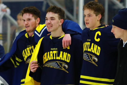 Hartland hockey players (left to right) Brenden Tulpa, Gabe Anderson and Joey Larson wait to receive their state Division 2 hockey championship medals after beating Trenton, 4-0, on Saturday, March 9, 2019 at USA Hockey Arena.