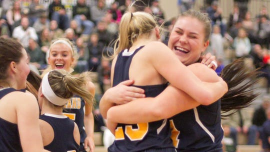 Tess Klavon, right, and Whitney Sollom celebrate the Eagles' win over Howell in the district championship game Friday, March 8, 2019.