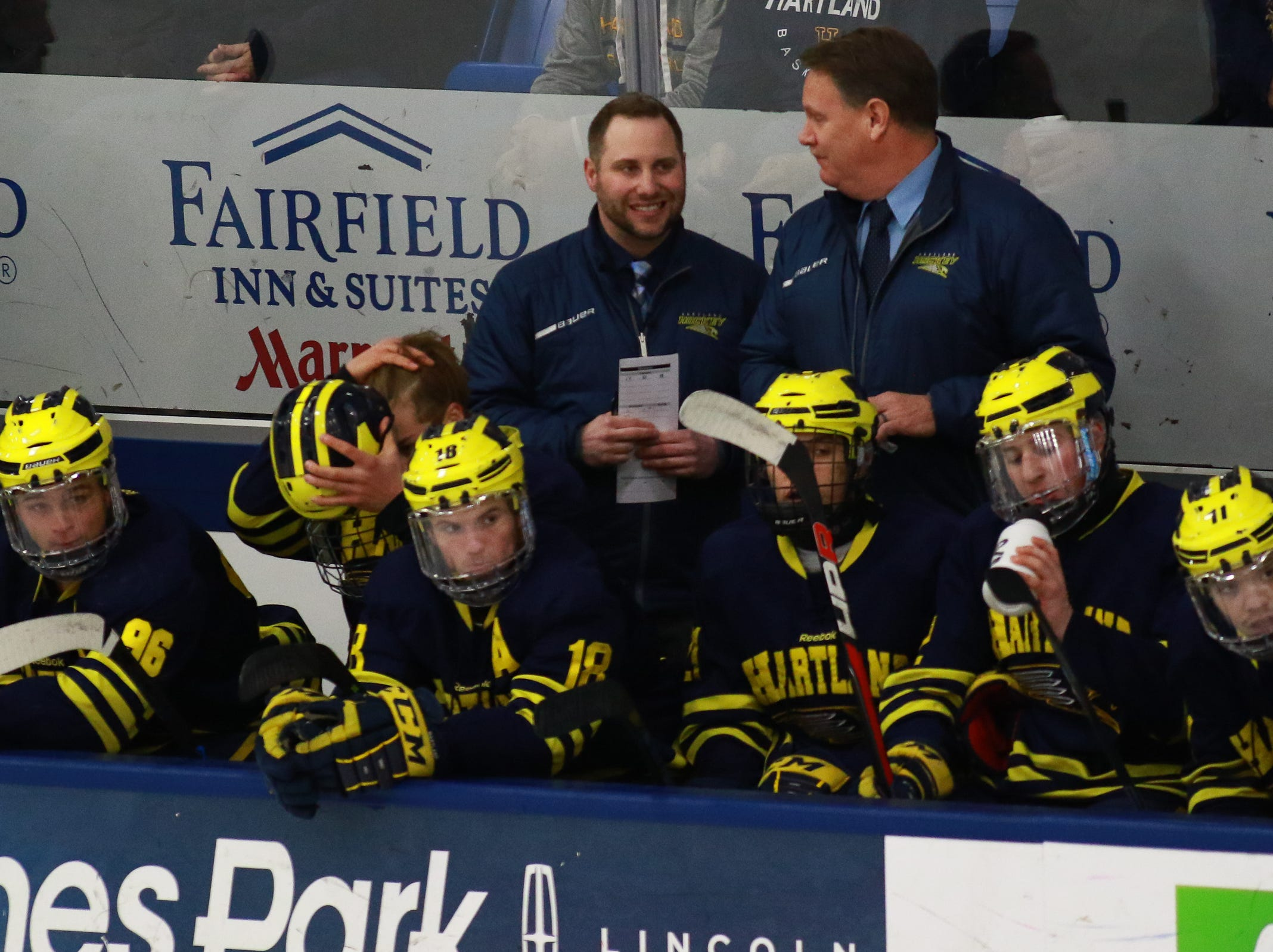 Hartland Rich Gadwa (left) smiles while talking with assistant coach John McCullough during a 4-0 victory over Trenton in the state Division 2 championship hockey game on Saturday, March 9, 2019 at USA Hockey Arena.