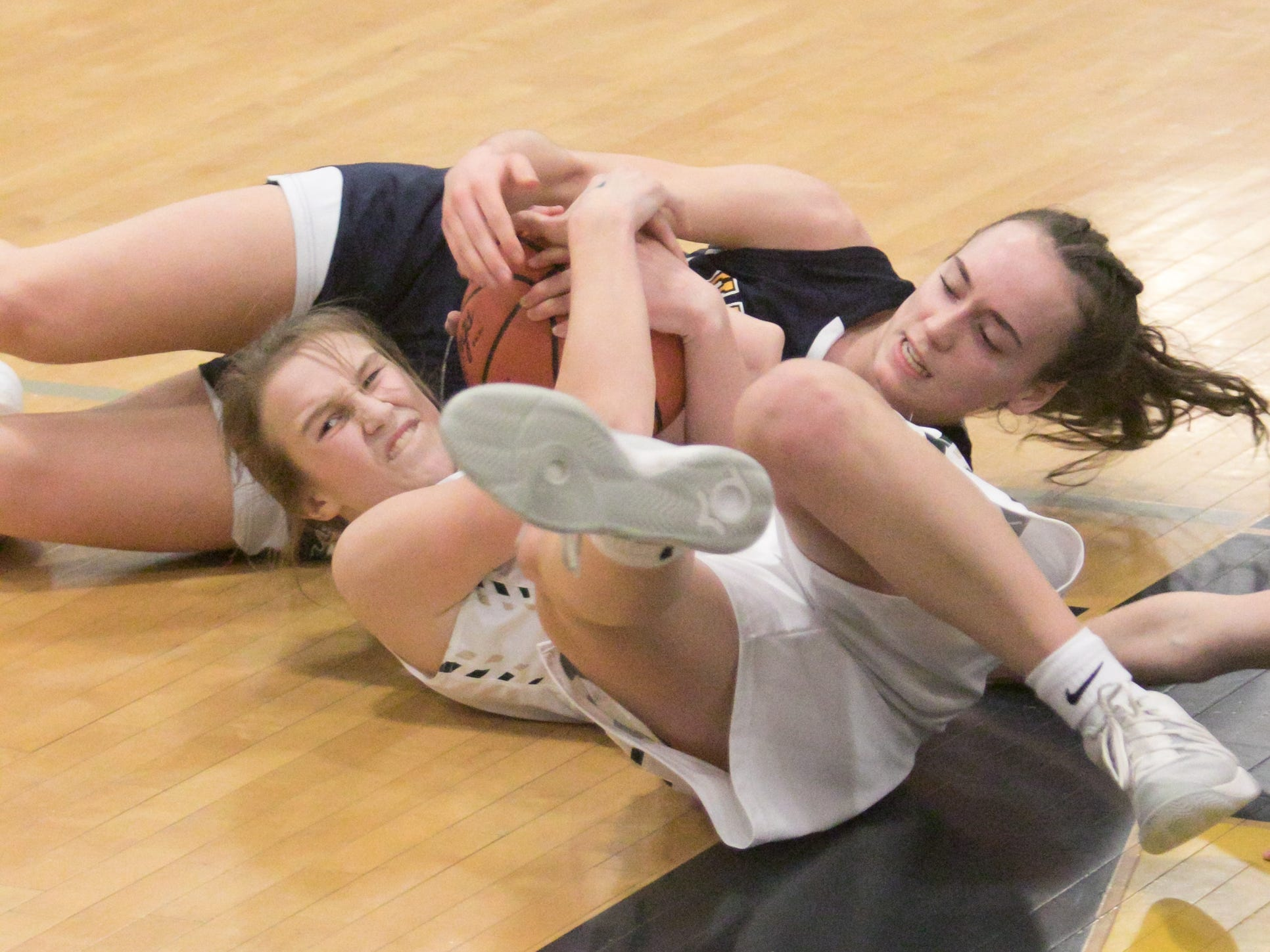 Howell's Allison Pennala, with head to left, and Hartland's Madi Moyer grapple for the ball in the district championship game Friday, March 8, 2019.