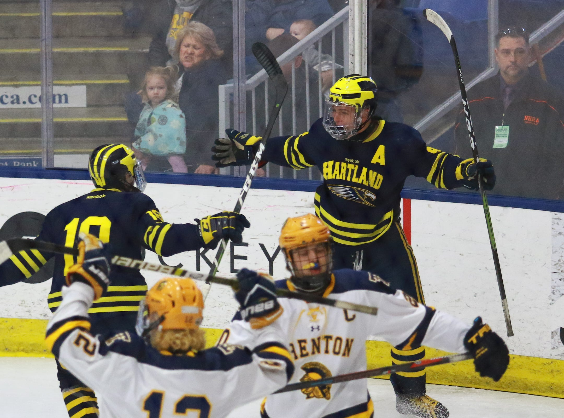 Hartland's Owen Pietila (right) and Brenden Tulpa (18) celebrate Pietila's first goal in a 4-0 victory over Trenton in the state Division 2 championship hockey game on Saturday, March 9, 2019 at USA Hockey Arena.