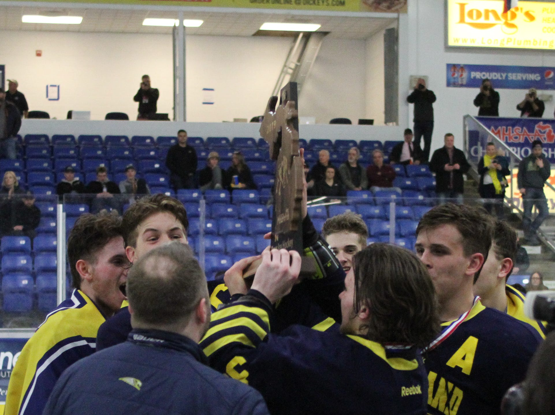 Hartland hoists the trophy after a 4-0 victory over Trenton in the state Division 2 championship hockey game on Saturday, March 9, 2019 at USA Hockey Arena.