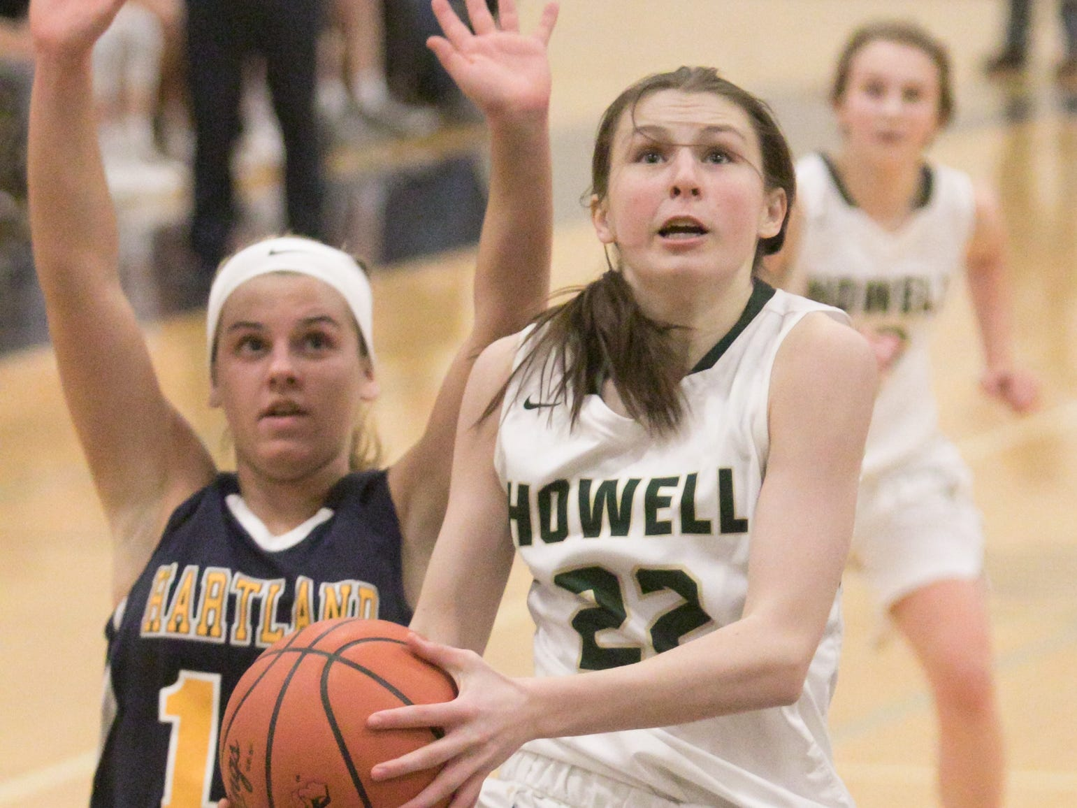 Howell's Maeve St. John drives past Hartland's Nikki Dompierre to score in a district championship game loss to the Eagles on Friday, March 8, 2019.