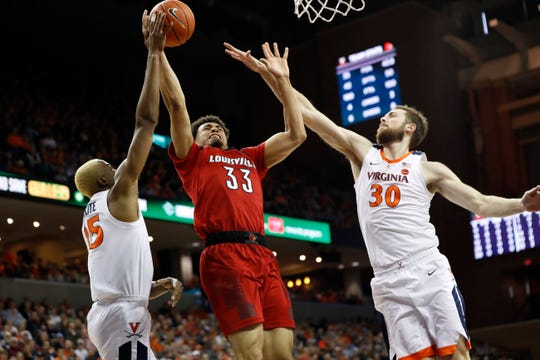 Louisville Cardinals forward Jordan Nwora (33) shoots the ball as Virginia Cavaliers forward Mamadi Diakite (25) and Cavaliers forward Jay Huff (30) defend in the first half at John Paul Jones Arena in Charlottesville, Virginia, on Saturday, March 9, 2019.
