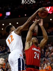 Virginia guard De'Andre Hunter (12) blocks the shot of Louisville forward Dwayne Sutton (24) during the first half of an NCAA college basketball game in Charlottesville, Va., Saturday, March 9, 2019.