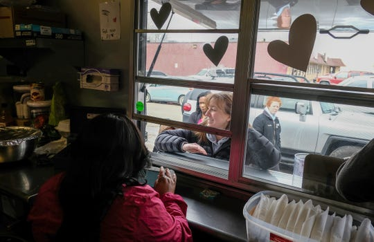 Customers line up before DeAnna Ray-Brown opens for business at her food truck to buy her cheesecake Saturday, March 9, 2019.