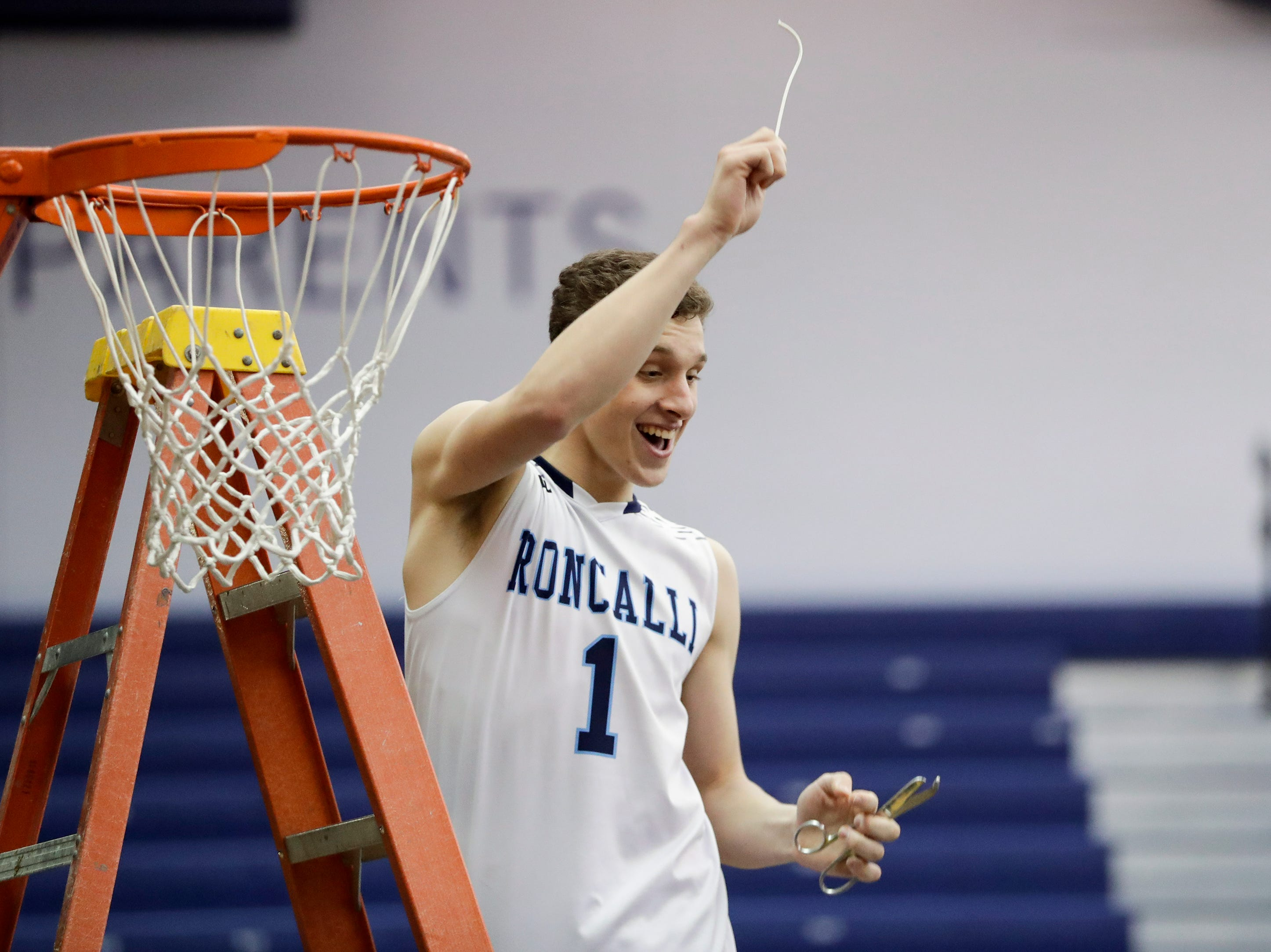 Roncalli's Daniel Burgarino (1) cuts the net after the Jets defeat Milwaukee Academy of Science for a WIAA Division 4 sectional championship 81-53 at Sheboygan North High School Saturday, March 9, 2019, in Sheboygan, Wis. Joshua Clark/USA TODAY NETWORK-Wisconsin