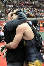 Northmor junior Conor Becker and coach Scott Carr embrace after Becker wins his semifinal match Friday to earn a shot at a Division III title at 170 pounds in the state wrestling tournament.