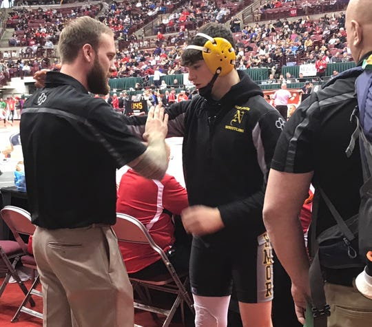 Northmor assistant coach Jamie Baldridge, a state runner-up for the school in 2014, helps Tony Martinez get loose before one of his matches Saturday at the state wrestling tournament.