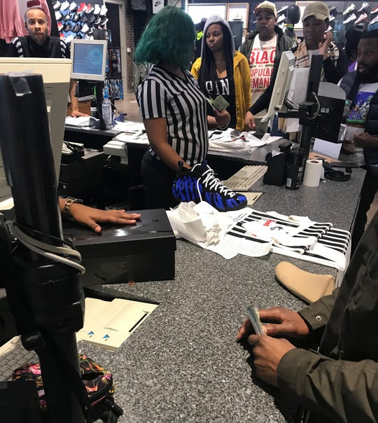 Customers wait in line to purchase the Tiger-themed Foamposite shoes Saturday morning at Foot Locker in Wolfchase Galleria.