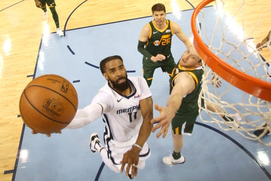 Memphis Grizzlies guard Mike Conley lays the ball up past Utah Jazz forward Joe Ingles during their game at the FedExForum on Friday, March 8, 2019.