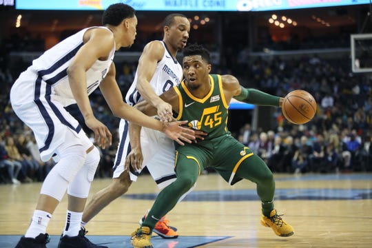 Memphis Grizzlies guard Avery Bradley, center, and Ivan rabb defend Utah Jazz guard Donovan Mitchell during their game at the FedExForum on Friday, March 8, 2019.