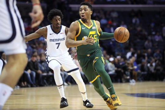 Utah Jazz guard Donovan Mitchell drives past Memphis Grizzlies forward Justin Holiday during their game at the FedExForum on Friday, March 8, 2019.