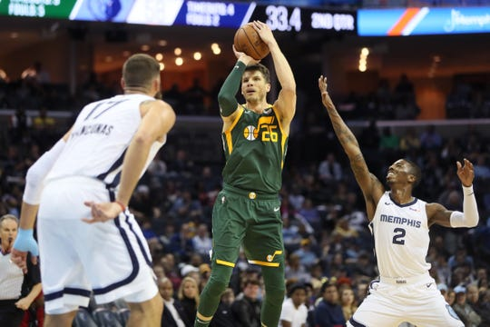 Utah Jazz forward Kyle Korver shoots the ball over the outstretched hand of Memphis Grizzlies guard Delon Wright during their game at the FedExForum on Friday, March 8, 2019.