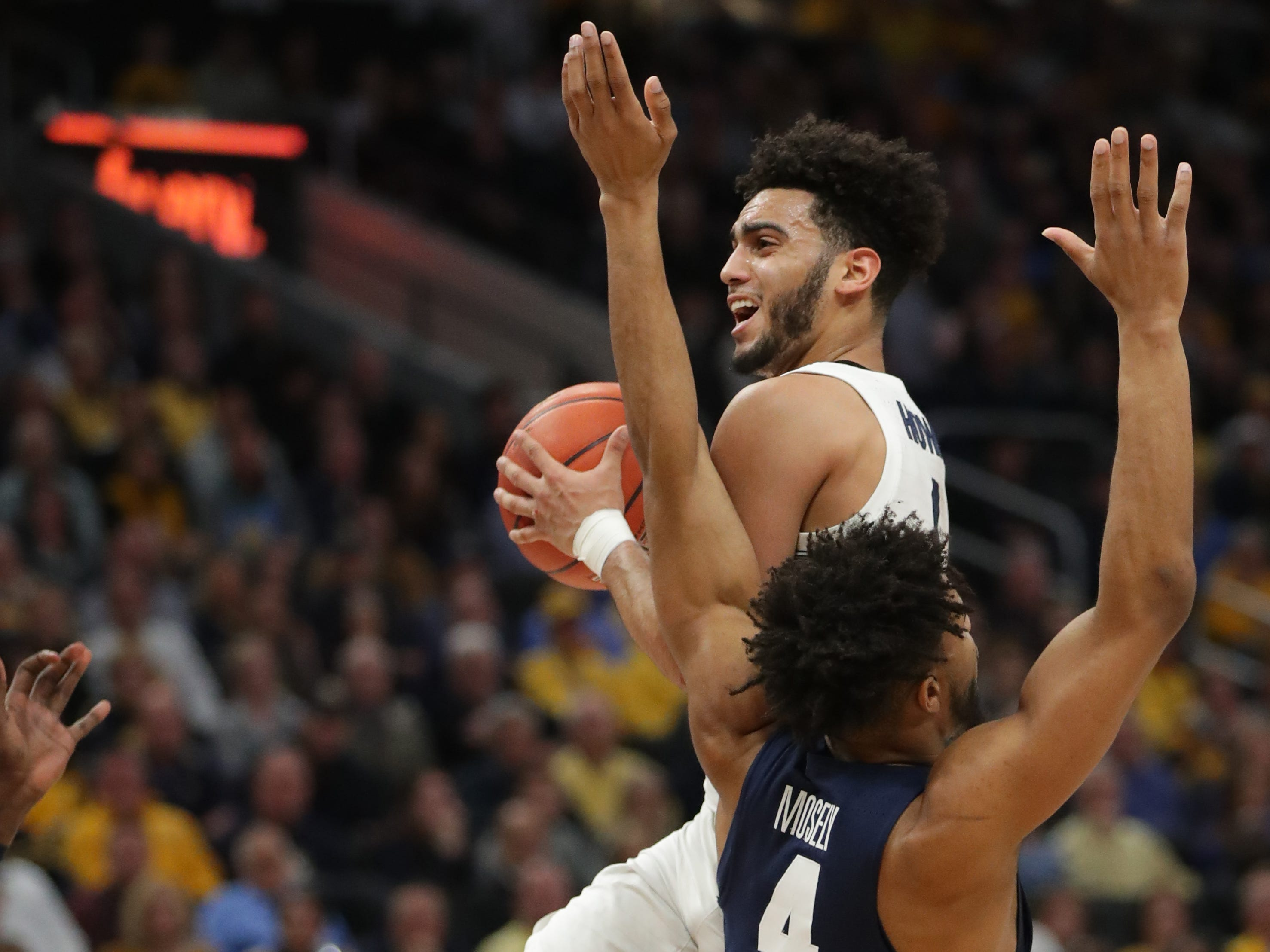 Marquette guard Markus Howard collides with Georgetown guard Jagan Mosely.