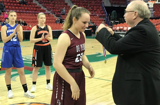 De Pere's Natalie Cerrato receives a medal after finishing fourth in the WIAA girls basketball 3-point Challenge at the Resch Center in Ashwaubenon on March 9.