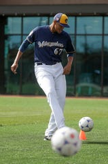 Angel Perdomo runs a drill with a soccer ball during a Brewers spring training baseball workout.