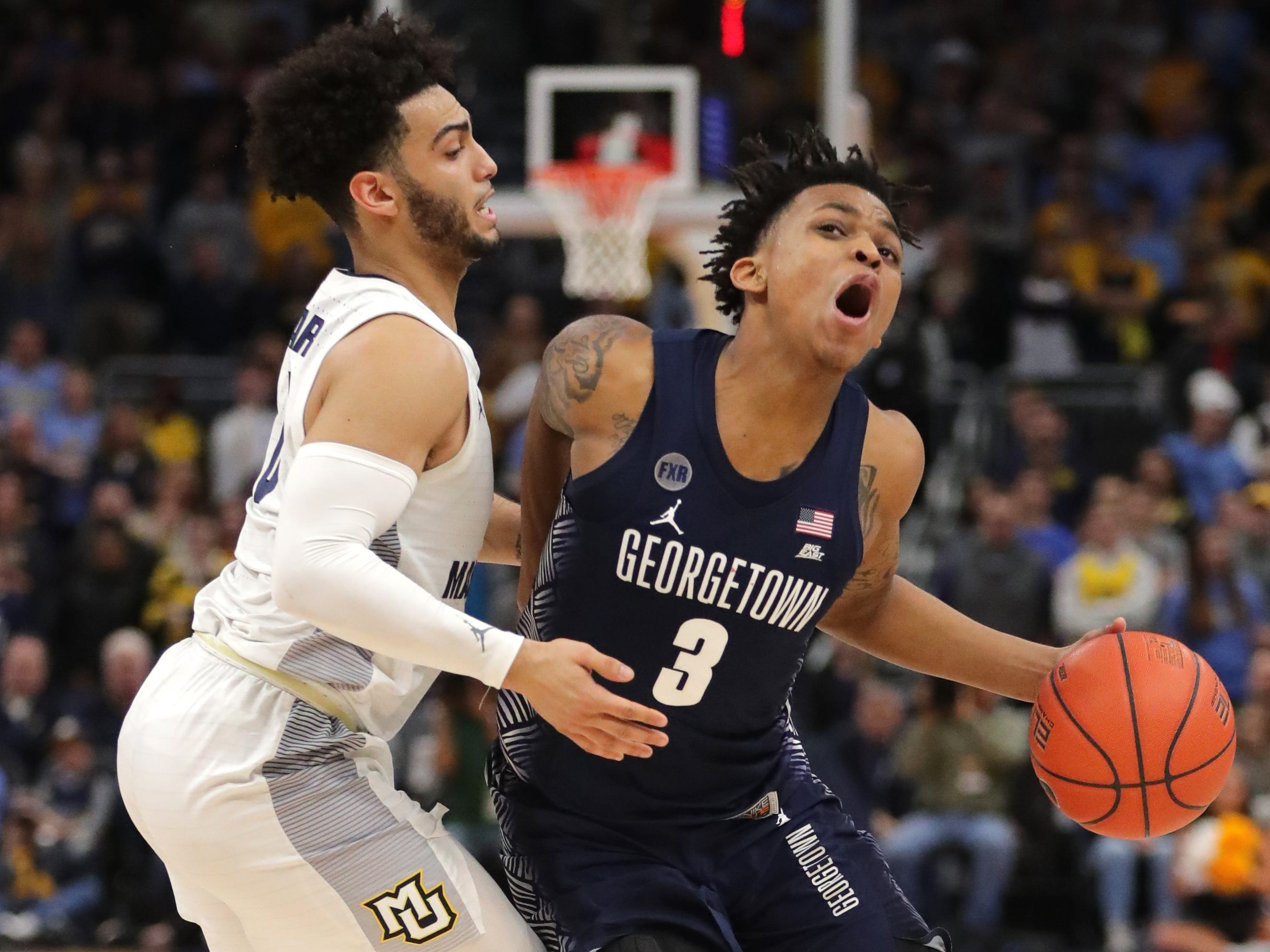 Marquette guard Markus Howard fouls Georgetown guard James Akinjo during the second half.